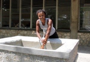 A woman washes her hands at a basin on HAS' campus. Without these fountains, many in the area would not have access to potable water.